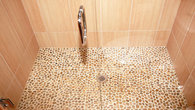 Bathroom downstairs with pebble stone floor behind the glass